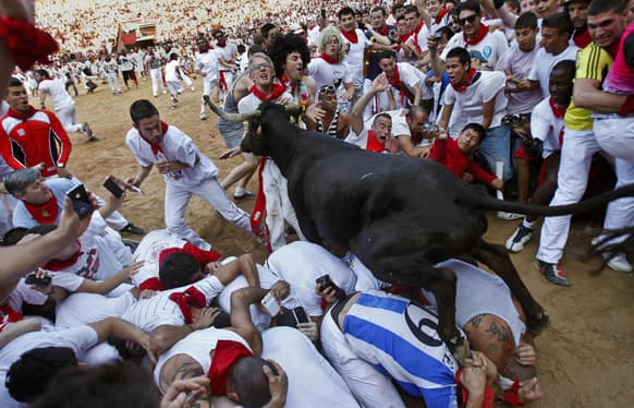 A cow jumps over revelers lying down on the bull ring as one of them is pushed by the animal at the end of the fifth run of the famed San Fermin festival, in Pamplona northern Spain.