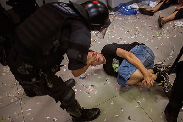 An activist of Mortgage Victims` Platform (PAH) argues with a riot police officer after occupying a bank as part of a protest to support a neighbor who is facing an eviction process in Barcelona, Spain.