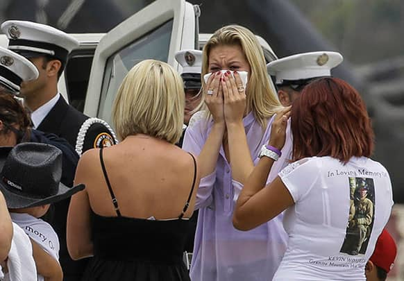 Mourners of fallen firefighter, Kevin Woyjeck, grieve at the coffin carrying his remains after arriving aboard a C-130 transport plane at the Los Alamitos Army Airfield at the Joint Forces Training Base in Los Alamitos, Calif.