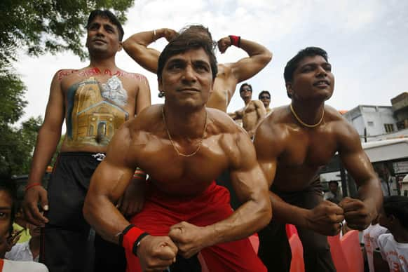 Men flex their muscles as they participate in the annual chariot procession of Hindu god Lord Jagannath in Ahmadabad.