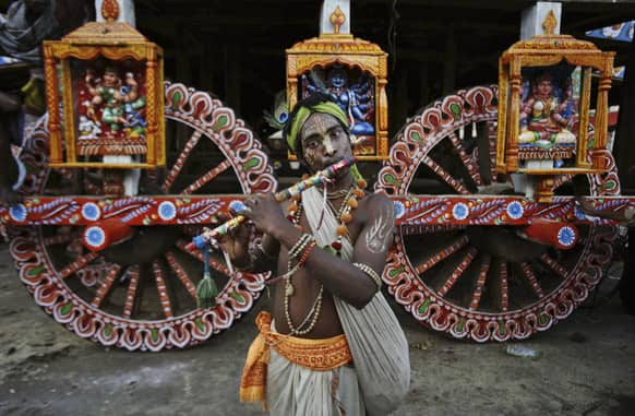 A devotee dressed as Lord Krishna plays the flute ahead of the annual Rath Yatra or Chariot procession of Lord Jagannath in Puri, 60 kilometers (37 miles) from the eastern Indian city of Bhubaneswar.