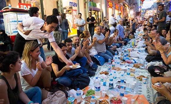 Thousands of people sit on Istiklal Avenue, the main shopping road of Istanbul, in Istanbul, Turkey.