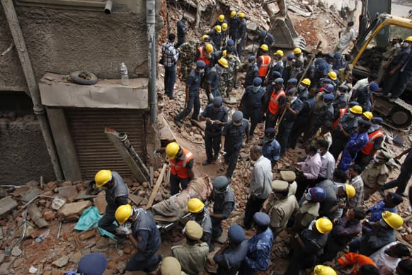 Rescue workers carry the body of a victim of a building that collapsed in Hyderabad.