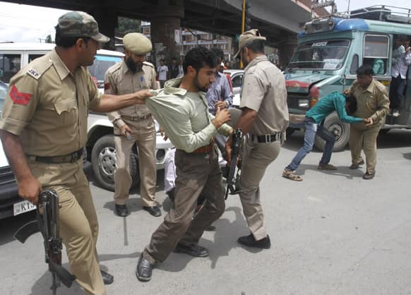 Policemen detain Kashmiri government employees during a protest in Srinagar. The protesters were demanding regularization of contractual jobs and a hike in salary.