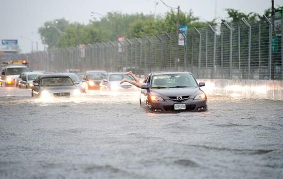 A woman gets back in her car in flood water on Lakeshore West during a storm in Toronto.