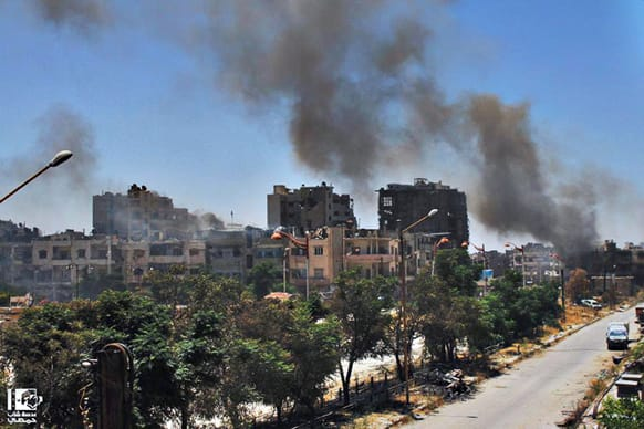 Citizen journalism image provided by Lens Young Homsi, which has been authenticated based on its contents and other AP reporting, black smoke rises from buildings damaged by Syrian government airstrikes and shelling in Homs, Syria.