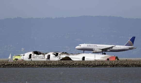 A United Airlines plane lands next to the wreckage of Asiana Flight 214 at the San Francisco International Airport in San Francisco.