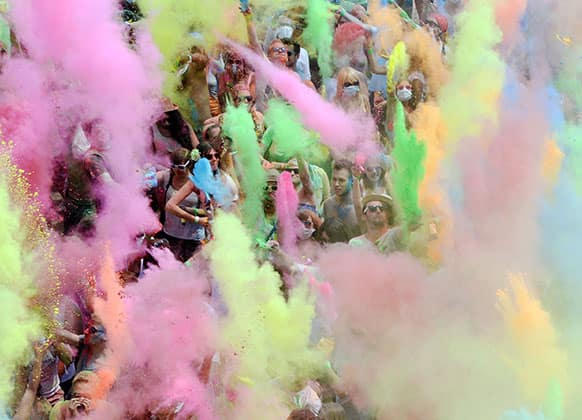 Visitors of the Holi Festival of Colours throw special colored powders in the air on a meadow near Karlsruhe, Germany.