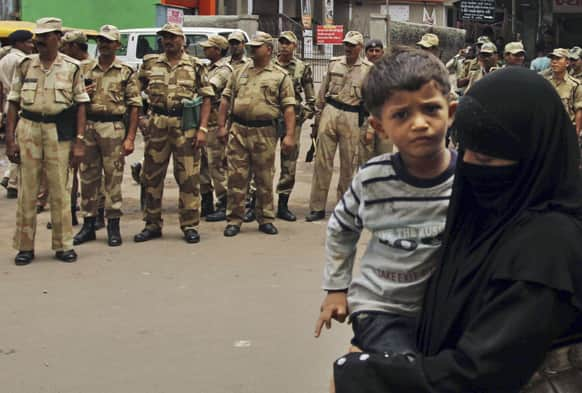 An Indian muslim woman with her child walks past paramilitary soldiers manning on a street ahead of the annual Rath Yatra or Chariot procession of Lord Jagannath in Ahmadabad.