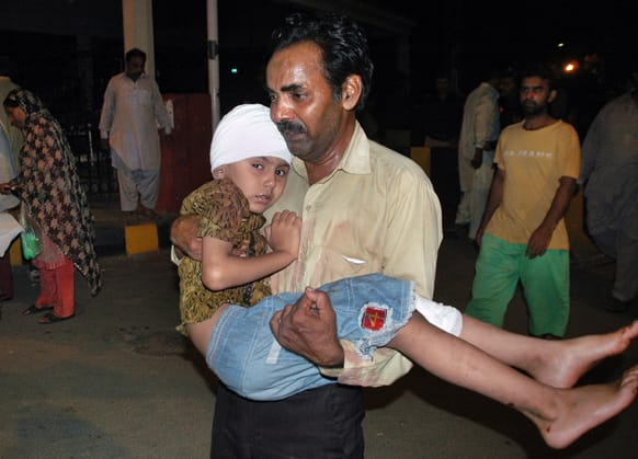 A Pakistani carries his son who was injured in a bomb blast after the boy receives initial treatment at a local hospital in Lahore, Pakistan.