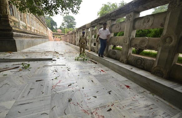 A security officer inspects the site of an explosion as blood lies splattered around the Bodhi tree, under which Buddha is believed to have achieved enlightenment, at the premise of the Mahabodhi Temple.