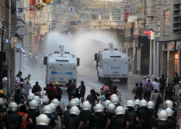 Police uses water cannons against protesters as media and riot policemen run behind the trucks in Istiklal Street, Istanbul`s main shopping strip, during clashes.