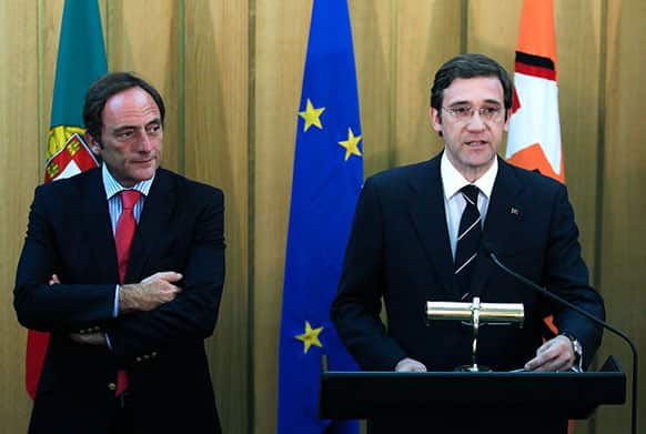 Portugal`s Prime Minister and leader of the Social Democrat Party, PSD, Pedro Passos Coelho, right, gives an statement next to Portugal`s Foreign Minister and leader of Popular Party, CDS, Paulo Portas following their meeting in Lisbon.