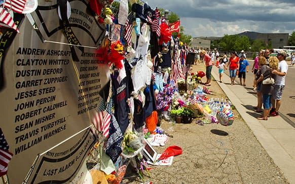 Items are displayed at a makeshift memorial at the Fire Station No. 7 memorial for fallen firefighters in Prescott, Ariz.