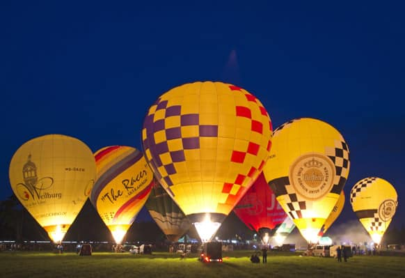 Hot air balloons glow in the evening light during the international balloon festival `Montgolfiade` in Heldburg, central Germany.