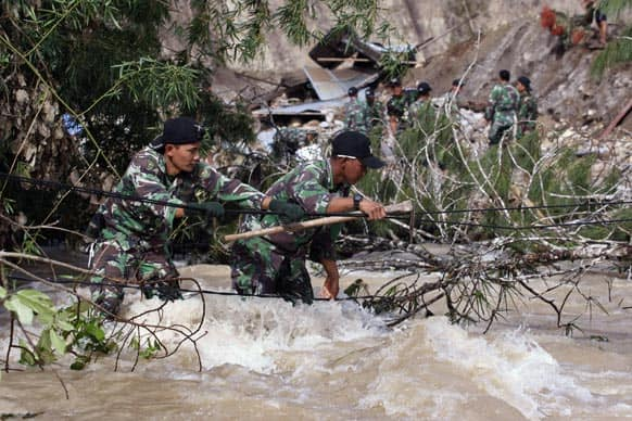 Indonesian soldiers use a rope to cross a swollen river as they search for victims of a landslide triggered by Tuesday`s earthquake in Serempah, Aceh province.