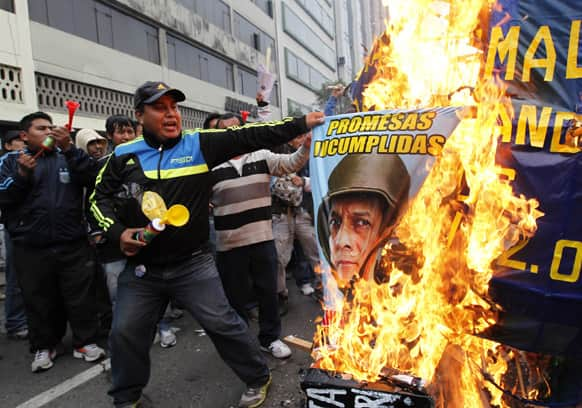 A construction worker burns a poster with the image of Peru`s President Ollanta Humala, during a protest against a new civil service law that will require public sector employees to undergo work evaluations periodically, in Lima, Peru.