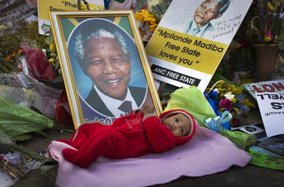 Oamohetswe Mabitsela, 4 months old, is placed by his mother next to a picture of Nelson Mandela for her to take a photograph of him with her camera phone, outside the Mediclinic Heart Hospital where former South African President Nelson Mandela is being treated in Pretoria.
