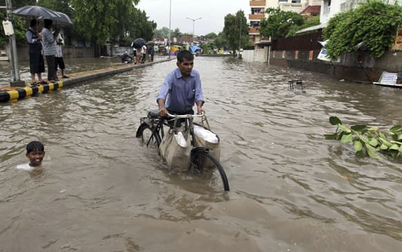 A child swims beside a man pushing his cycle past a flooded road after heavy rain lashed the city in Ahmadabad.