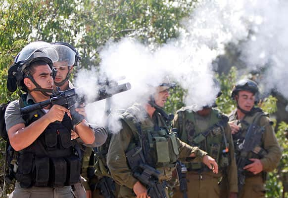An Israeli border policeman fires a tear gas canister during a protest against an Israeli roadblock at the entrance to the West Bank village of Beitin, near Ramallah.