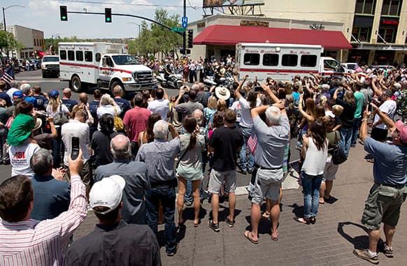 A crowd gathers to greet the Granite Mountain Hotshot crew trucks as they are driven through downtown Prescott, Ariz.