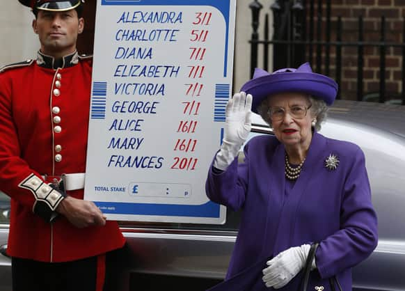 As part of a publicity stunt, people from a bookmakers office dressed as Britain`s Queen Elizabeth II and a British Guardsman stand with a placard with the odds for the name of the royal baby as they pose for the media outside St. Mary`s Hospital exclusive Lindo Wing in London.