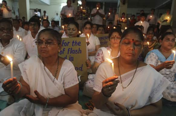 People hold candles as they pray for the victims of Uttarakhand floods, at a temple in Ahmadabad.