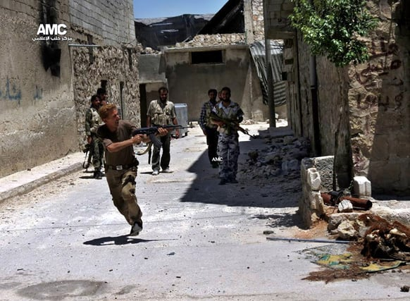 A Syrian rebel fires his weapon during heavy clashes with Syrian soldiers loyal to Syrian President Bashar Assad near Aleppo International Airport in Aleppo, Syria.