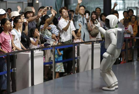 Honda Motor Co.'s interactive robot Asimo gestures while talking with visitors at a demonstration event at the Miraikan science museum, in Tokyo.