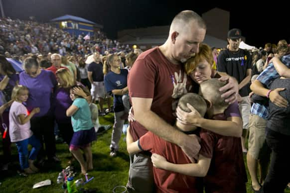 Fred Dangler and Nicole Gambill of Prescott, Ariz. embrace their children Evan, 9, right and Aidan, 8, during a candlelight vigil for the 19 firefighters killed battling the Yarnell Hill Fire, on the football field at Prescott High School in Prescott.