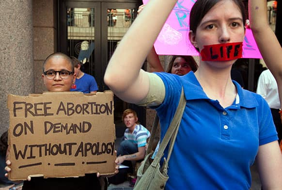Pro-abortion rights supporter Yatzel Sabat, left, and anti-abortion protestor Amanda Reed demonstrate at the state Capitol in Austin, Texas.