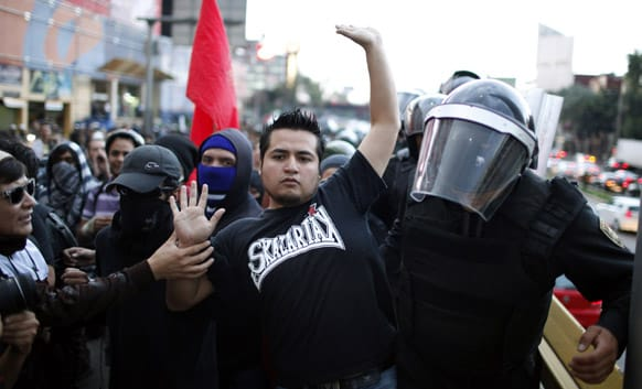 A demonstrator tries to walk on the sidewalk as police try force their way through the crowd during a march to protest against what they claim is an alleged government plan to privatize PEMEX, the state-owned oil company and also to mark the one year anniversary of the election of Mexican President.