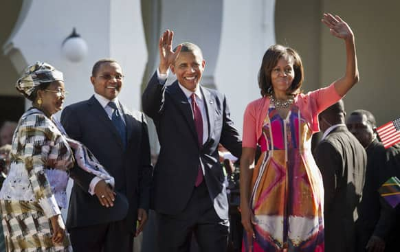 US President Barack Obama, and first lady Michelle Obama, wave as they enter State House accompanied by Tanzanian President Jakaya Kikwete, center-left, and Tanzanian First Lady Salma Kikwete, in Dar es Salaam, Tanzania.