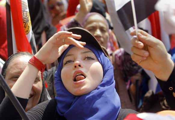 An Egyptian protester ululates and waves a national flag during a demonstration against Egypt`s Islamist President Mohammed Morsi in Tahrir Square in Cairo.