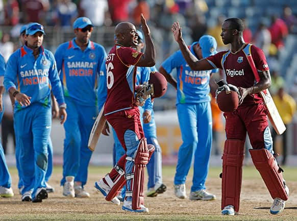 West Indies` Tino Best, front left, high fives with his batting partner Kemar Roach after they beat India by one wicket in their Tri-Nation Series cricket match in Kingston, Jamaica.