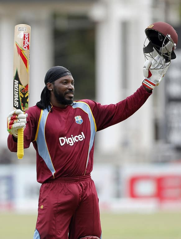 West Indies opening batsman Chris Gayle raises his bat and helmet after scoring a century during the Tri-Nation Series cricket match against Sri Lanka in Kingston, Jamaica.