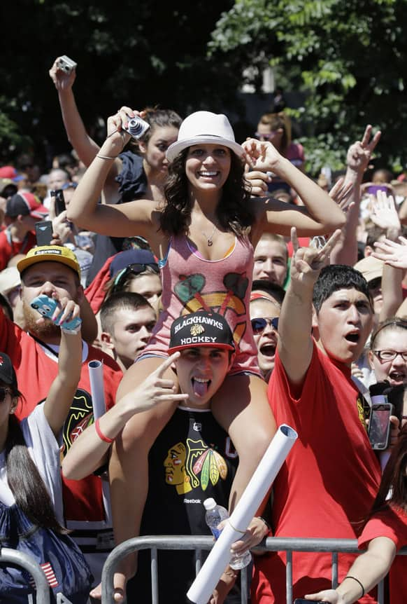 Fans cheer along the parade route as buses carrying the Stanley Cup champion Chicago Blackhawks passes in Chicago.