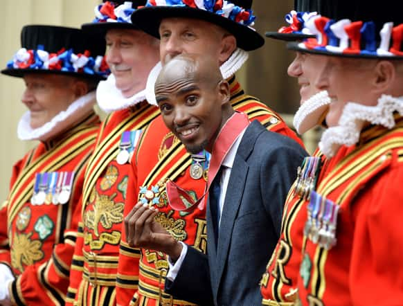 Double Olympic gold medallist athlete Mo Farah smiles with his CBE medal after receiving the award from Britian`s Prince Charles at Buckingham Palace in central London.