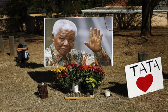 A young boy rests by a large picture of former South African President Nelson Mandela placed by the Union Building in Pretoria, South Africa.