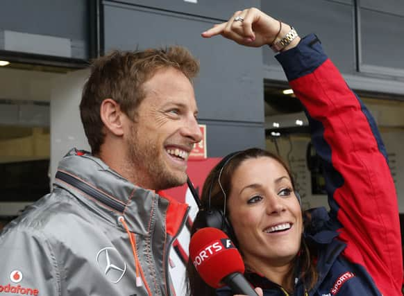 McLaren Mercedes driver Jenson Button of Britain jokes with a member of the media while he is being interviewed, during the first practice at the Silverstone circuit, England.