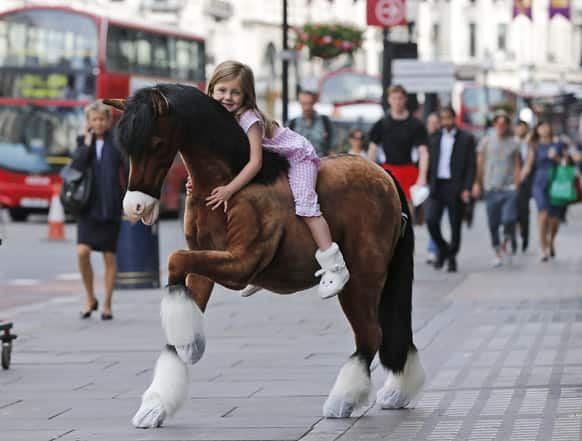 Five year old Lottie poses for photographers on the Clydesdale Prancing Pony in front of the toy store Hamleys in London.