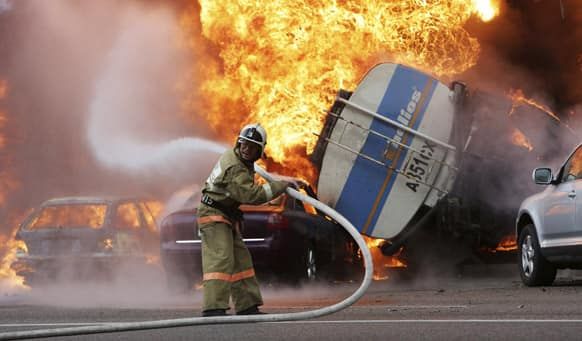 A firefighter tries to extinguish a fire after a road accident in downtown Almaty.