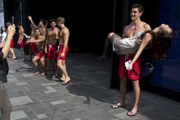 A Chinese women acts fainted as she poses a photo session with a lifeguard model outside the new Hollister Co. clothing store, which to open on June 29, during a promotion event at a commercial district in Beijing, China.