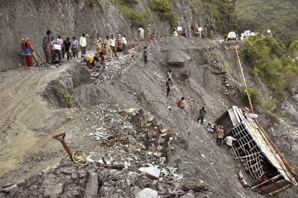 People gather near a truck carrying LPG cylinders that fell in the Bhagirathi River from a road damaged after monsoon flooding in Uttarkashi.