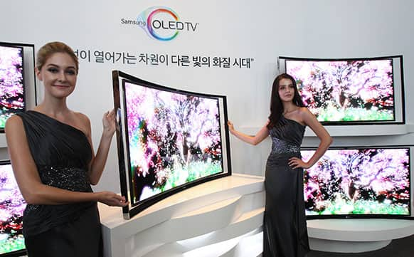 Models pose with a Samsung Electronics Co.`s 55-inch curved OLED TV during a press conference at its headquarters in Seoul, South Korea.