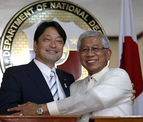 Japanese Defense Minister Itsunori Onodera, left, and his Philippine counterpart Voltaire Gazmin pose for photographers following their joint news conference at Camp Aguinaldo at suburban Quezon city, northeast of Manila, Philippines.