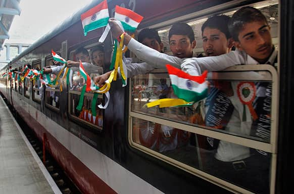Young Indian school children displaythe national flag as they wave from inside the first train connecting Qazigund to Banihal during its inauguration, in Banihal some 120 kilometers (75 miles) south of Srinagar.