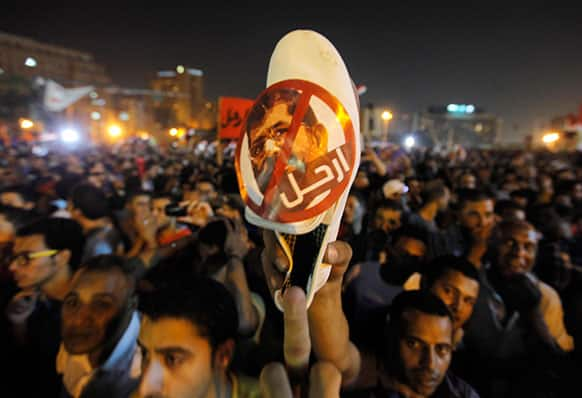 An Egyptian protester raises a shoe with a picture of Egyptian President Mohammed Morsi with Arabic that reads: