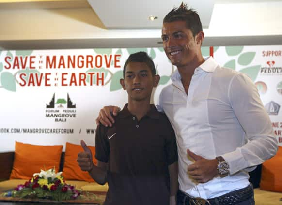 Cristiano Ronaldo poses with a fan named Martunis during a press conference in Kuta, Bali, Indonesia. Martunis was an Aceh tsunami survivor, who was reportedly found floating in the sea wearing a Portugal national soccer team`s jersey.