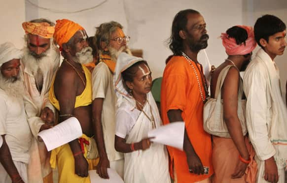 Hindu holy men and a woman stand in a queue for a medical check up before they register for the annual pilgrimage to the Amarnath cave shrine in Jammu.